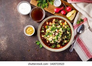 Cold Russian Soup Okroshka with sausage, vegetables and kvass in bowl and raw ingredients on dark table. Top view. Space for text.