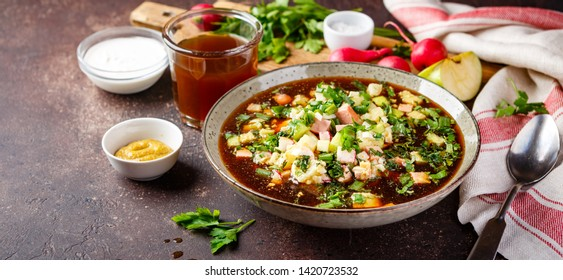 Cold Russian Soup Okroshka with sausage, vegetables and kvass in bowl and raw ingredients on dark table. Long wide banner. Space for text. Long wide banner