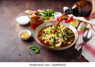 Cold Russian Soup Okroshka with sausage, vegetables and kvass in bowl and raw ingredients on dark table