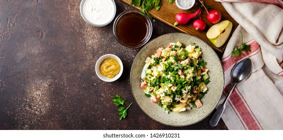 Cold Russian Soup Okroshka with sausage, vegetables and kvass in bowl and raw ingredients on dark table. Top view. Space for text. Long wide banner. Long wide banner
