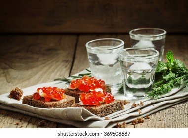 Cold Russian vodka with ice and small snacks sandwiches with butter and red salmon caviar on an old wooden table in rustic style, selective focus