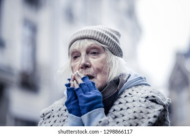 So cold. Sad aged woman standing on the street while trying to warm her hands
