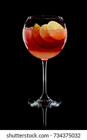 Cold sangria in a wine glass with reflection on black background