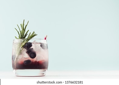 Cold shot in glass with blueberry, ice cubes, rosemary, straw in trendy modern bar interior in pastel mint color on white wood board, copy space.