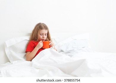 cold sick child laying on bed and drinking a cup of tea