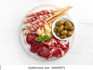 Cold smoked meat and cheese plate with olives and bread sticks on white wooden background. From top view