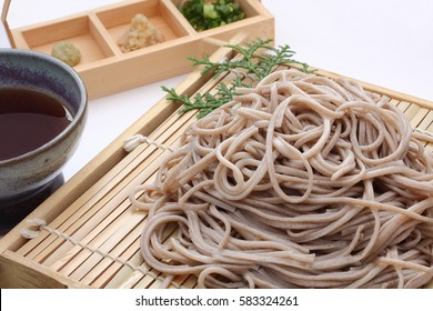 Cold soba [buckwheat noodles] served on a wickerwork platter and eaten after being dipped in a cold sauce/ Chilled Buckwheat Noodles Soba , Japanese food