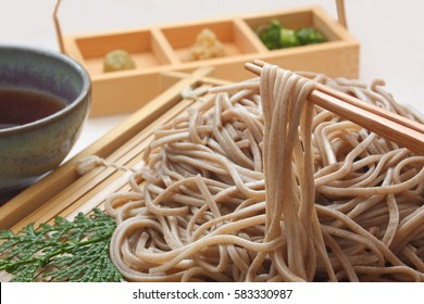 Cold soba [buckwheat noodles] served on a wickerwork platter and eaten after being dipped in a cold sauce/Eatiing Chilled Buckwheat Noodles Soba with chopsticks , Japanese food