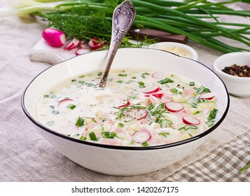 Cold soup with fresh cucumbers, radishes, potato and sausage with yoghurt in bowl. Traditional russian food - okroshka. Summer cold soup.
