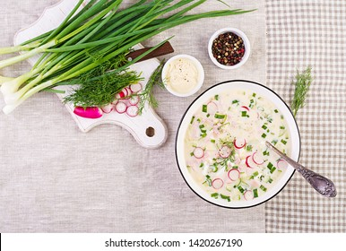Cold soup with fresh cucumbers, radishes, potato and sausage with yoghurt in bowl. Traditional russian food - okroshka. Summer cold soup. Top view. Flat lay