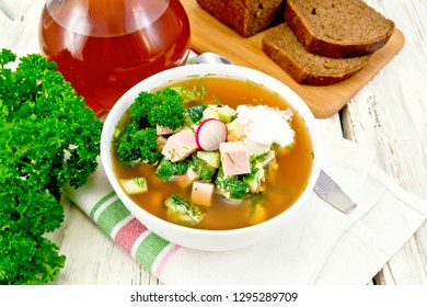 Cold soup okroshka from sausage, potatoes, eggs, radish, cucumber, greens and kvass in a white bowl on napkin, bread and jug with drink on the background of light wooden board
