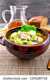 Cold soup okroshka from sausage, potatoes, eggs, radishes, cucumber, greens and drink of kvass in a clay bowl, bread on wicker napkin on wooden board background