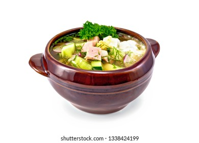 Cold soup okroshka from sausage, potatoes, eggs, radish, cucumber, greens and kvass drink in a clay bowl isolated on white background