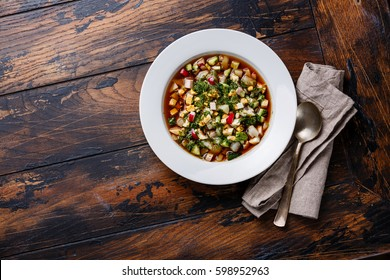 Cold Soup Okroshka with sausage, vegetables and kvass serving size on wooden table copy space