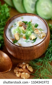 Cold soup Tarator with kefir in a wooden bowl. Bulgarian cuisine meal