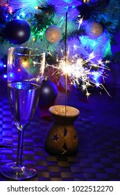 Cold sparklers and champagne on the background of a Christmas tree