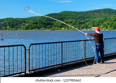Cold Spring, NY, USA August 21, 2011 A trapper casts his crab trap into the Hudson River from a pier in Cold Spring, New York
