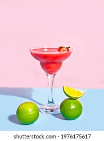 Cold strawberry margarita or daiquiri cocktail with lime and rum