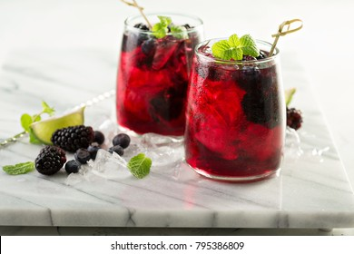 Cold summer berry drink with lime and blackberries