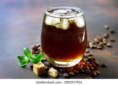 Cold summer cocktail with cola,whiskey and coffee liquor in a glass on a dark slate, stone or concrete background