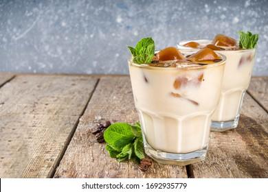 Café d'été froid, latte. Boisson de cocktail glacé au café avec glaçons, lait ou autres laits et feuilles de menthe surgelés. Espace de copie d'arrière-plan bois