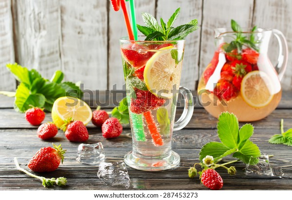 Cold summer drink with mint, strawberry and lemon