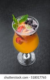 cold summer fruit cocktail on black table.fresh beverage