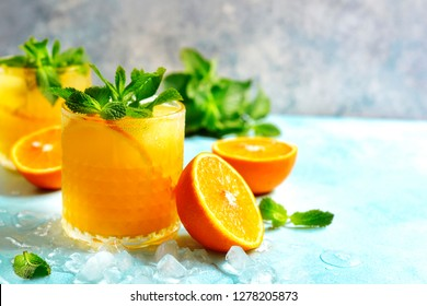 Cold summer orange lemonade with mint and ice cubes in a glass.
