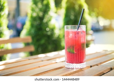 Cold summer refreshing cocktail on a wooden table in cafe outdoors