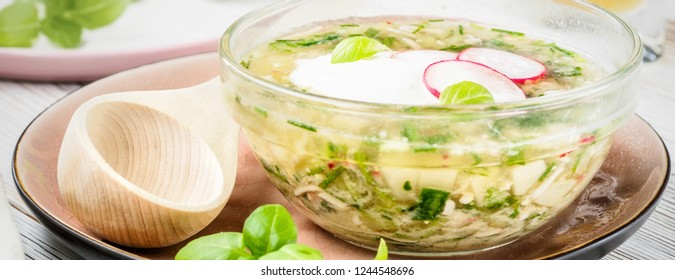 Cold summer soup okroshka traditional russian ukrainian from vegetables radish cucumber and green onions with beverages kvass on light wooden table served with rustic spoon and plate.