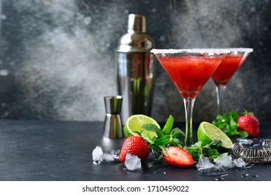 Cold summer strawberry cocktail with lime and mint ( mojito, margarita, rossini,daiquiri ) in a martini glasses on a dark slate, stone or concrete background..