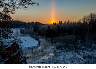 cold sunrise in winter forest with sun light pillar - an atmospheric optical phenomenon in which a vertical beam of light appears to extend above and/or below a light source
