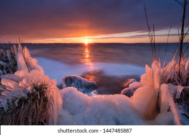 A cold sunset in winter on a frozen lake with a beautiful sky and sunbeams in the background - IJsselmeer, Friesland, The Netherlands
