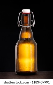 Cold swing top beer bottle with condensation of water drops on black