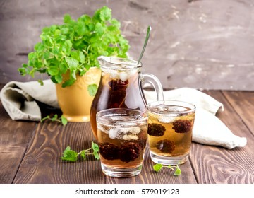 Cold tea with ice and fresh mint Wooden background