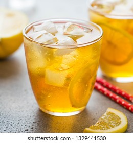 Cold tea with lemon and ice in a glass with drops, fresh sweet fruit drink, summer freshness, delicious lemonade