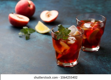 cold tea peach with ice in glasses on a blue background
