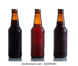 Cold unopened dark and amber beer bottles on white with reflection