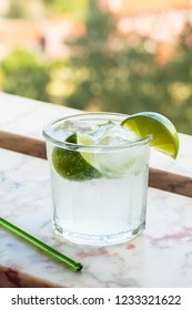 Cold Vodka or Gin and Tonic with Ice and Limes in Glass on Marble Windowsill