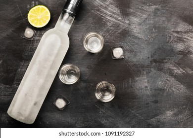 Cold vodka in shot glasses on a black background. Top view, copy space. Food background