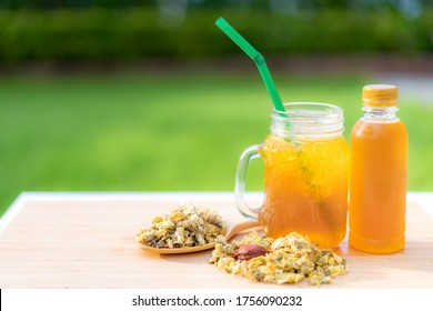Cold water of chrysanthemum flowers and dried chrysanthemum flowers on wooden table chinese Thai herb juice and refreshment cold drink.