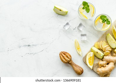 cold water with ice, ginger, mint, apple and lemon juice for summer healthy drink on white background top view mock-up