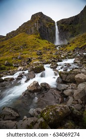 Cold water in Iceland. Waterfall in rocky mountains. Fresh and green grass. Beautiful mountain range in the backgrond.