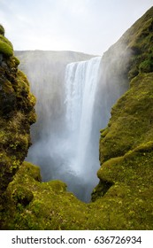 Cold water in Iceland. Waterfall in rocky mountains. Fresh and green grass. Beautiful mountain range in the background.