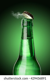Cold wet open beer bottle with smoke on green background