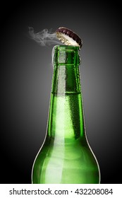 Cold wet open beer bottle with smoke on black background
