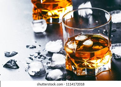Cold whiskey with ice cubes in black table, selective focus