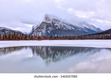 Cold Winter morning with low clouds on Mount Rundle reflecting off Vermilion Lakes in the Canadian Rockies of Banff National Park.