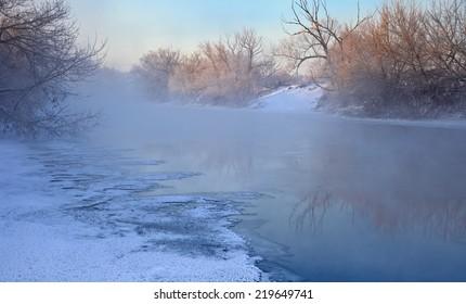 Cold winter sunrise panorama above foggy river. Beautiful winter Christmas landscape.