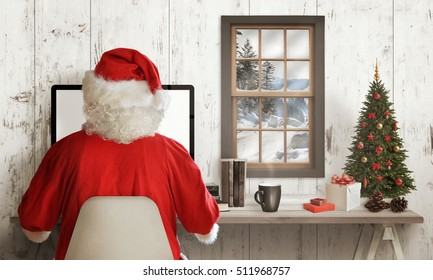 Cold winter time at Santa Claus home. Santa Claus work online on his computer. Gifts, Christmas tree and decorations on table. Snow outside through the window.